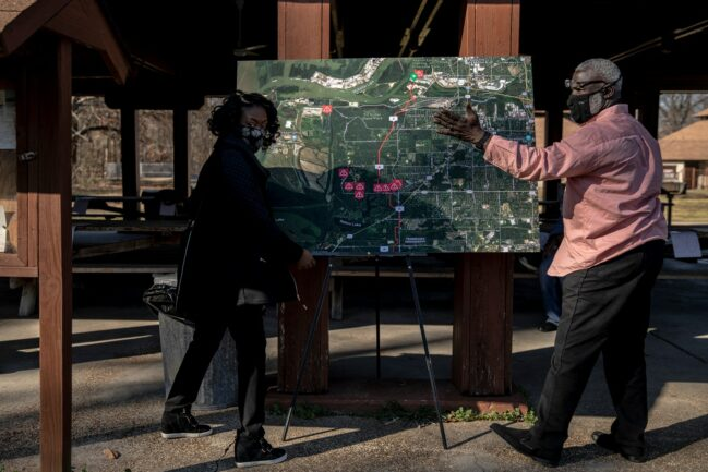 Kimberly Owens-Pearson (left) and Batsell Booker, president of the Boxtown Neighborhood Association (right) position a map with the proposed Byhalia Connection Pipeline Route near the shelter at T.O. Fuller State Park where they were helping to organize a community meeting about the project. (Photo: Andrea Morales for MLK50)