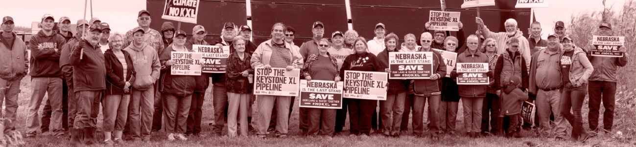 Group of people standing with signs that say Stop the Keystone XL Pipeline