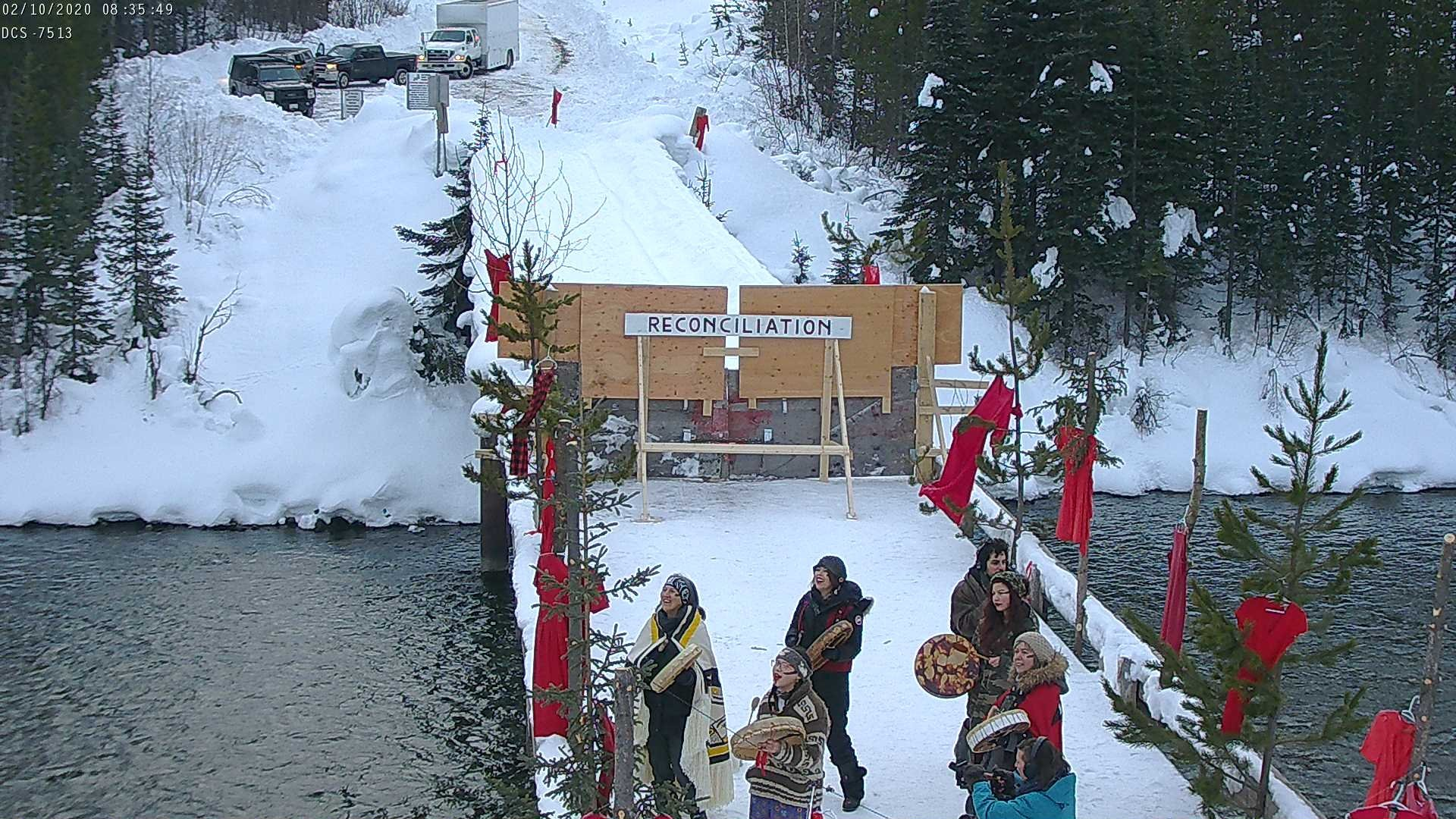 Image via Unist'ot'en Camp: RCMP are climbing the snow towards gate entrance, telling all present they will be arrested and face civil or criminal contempt. Matriarchs are calling the ancestors. February 2020